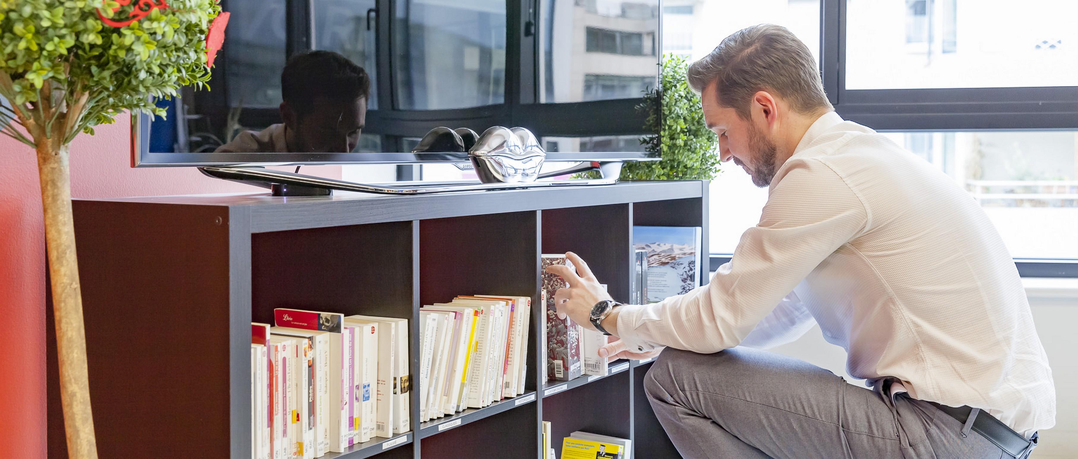 Un assistant daccueil rangeant une bibliothèque partagée