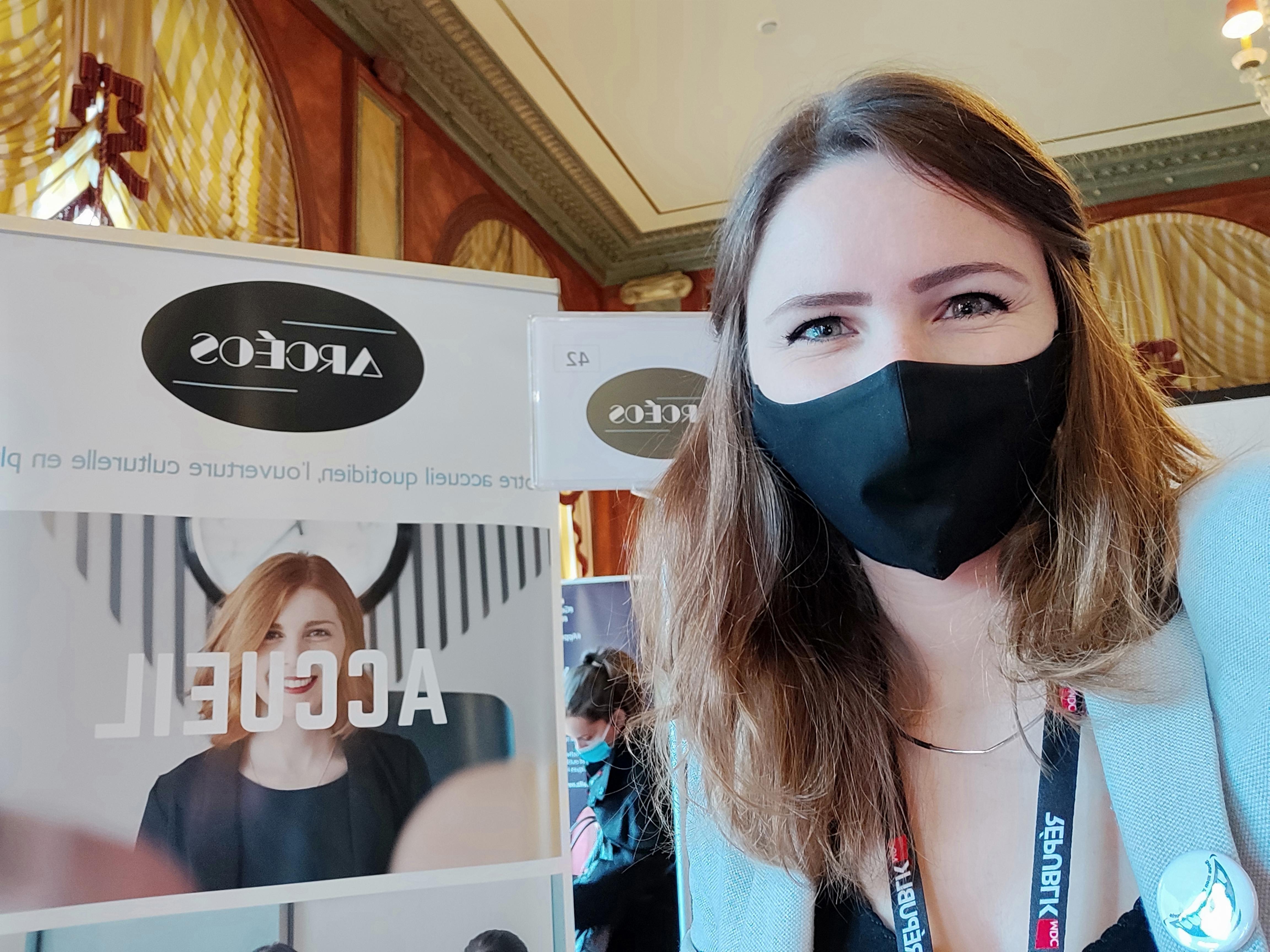 Agathe Roy, masquée devant le kakémono Arcéos au stand des FM' Days