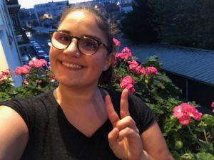 Selfie de Raquel devant des fleurs roses sur son balcon.