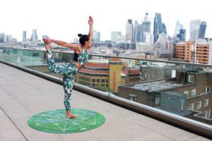 Femme faisant une pose de yoga sur une terrasse en face d'un centre-ville