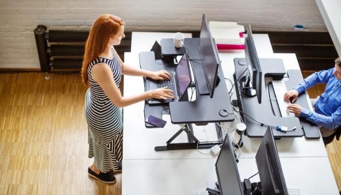 Femme devant un bureau assis-debout gardant son corps actif.